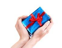 Les mains de la fille dans une forme d'un coeur donnant un cadeau Images libres de droits