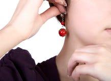Les mains de la fille retiennent une boucle d'oreille Photographie stock libre de droits