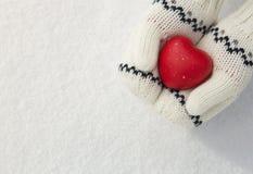 Les mains de la fille tenant le coeur rouge dans la neige Photos libres de droits