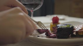 Les mains de la jeune femme coupant la viande fraîche savoureuse se trouvant du plat avec le légume utilisant la fin de fourchett banque de vidéos