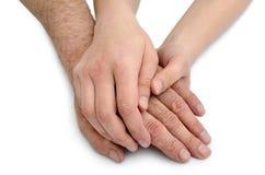 Les mains de la jeune femme tiennent des mains d'un vieil homme Photographie stock libre de droits