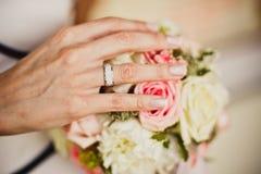 Les mains de la jeune mariée avec des fleurs Image stock