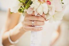 Les mains de la jeune mariée avec des fleurs Photos libres de droits