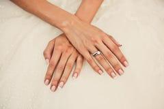 Les mains de la jeune mariée sur un dreww Photographie stock