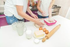 Les mains de la mère et de la fille malaxent la pâte pour la pizza photographie stock
