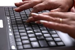 Les mains de la mi femme d'âge sur l'ordinateur portatif Image stock