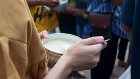 Les mains de la nourriture de offre de jeunes asiatiques dans l'aumône du ` s de moine roulent banque de vidéos