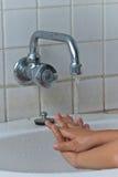 Les mains de lavage de garçon. Photo stock