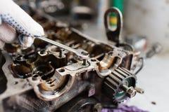 Les mains de mécanicien serrent l'écrou avec la clé tout en réparant le moteur Photos libres de droits