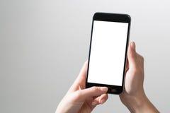 Les mains de maquette téléphonent le faux blanc haut de blanc d'affichage de participation d'écran photo libre de droits