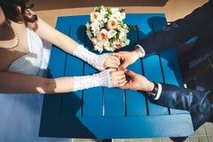 Les mains de mariage avec des anneaux et le bouquet se trouvent sur la table bleue, vue supérieure Photo stock