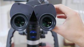 Les mains de personne installent l'oculaire du plan rapproché électronique moderne de microscope banque de vidéos