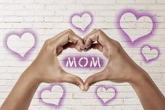 Les mains de personnes dans la forme du coeur avec la maman textotent Photographie stock libre de droits