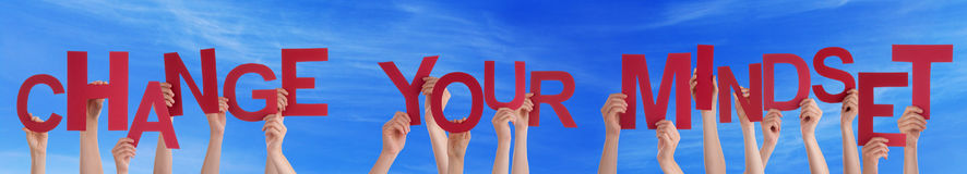 Les mains de personnes tenant Word rouge changent votre ciel bleu de mentalité Image libre de droits