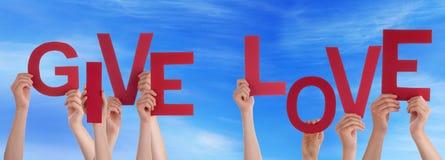 Les mains de personnes tenant Word rouge donnent à amour le ciel bleu Photographie stock libre de droits