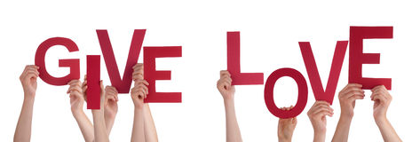 Les mains de personnes tenant Word rouge donnent l'amour Image stock