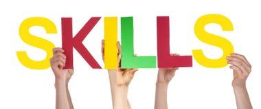 Les mains de personnes tiennent des qualifications droites colorées de Word Image stock