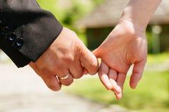 Les mains de plan rapproché d'un couple ont lié le foyer sur l'anneau Images libres de droits