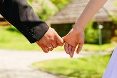 Les mains de plan rapproché d'un couple ont lié le foyer sur l'anneau Photographie stock