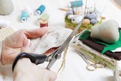 Les mains de plan rapproché de la couturière tiennent des ciseaux et coupent un tarte Photo libre de droits