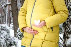 Les mains de plan rapproché de la femme enceinte tiennent un coeur neigeux image stock