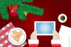 Les mains de Santa Claus tiennent le comprimé avec l'écran vide Image libre de droits