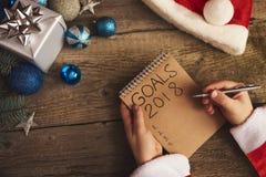 Les mains de Sata écrivant des buts pendant la nouvelle année Arbre de Noël et deco Image libre de droits