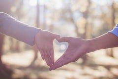 Les mains de tache floue des couples font le symbole de coeur dans le jardin avec le Saint Valentin de lumière du soleil Photo stock