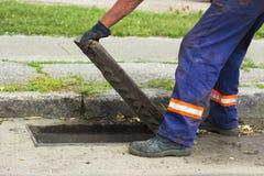 Les mains de travailleur ouvre un plan rapproché de grille de drain photo stock