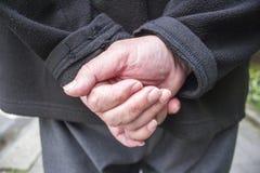 Les mains de vieil homme derrière le sien de retour Images stock