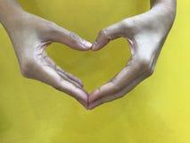 Les mains de Woman's font la forme de coeur avec le fond jaune Images stock