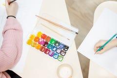 Les mains des enfants dessinant des images et des peintures colorées Le processus de la créativité d'enfance dans la salle de cla images stock