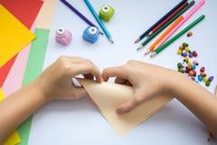Les mains des enfants font le loup d'origami du papier de pêche Image libre de droits