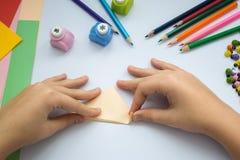 Les mains des enfants font le loup d'origami du papier de pêche Photographie stock