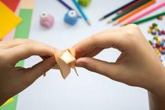Les mains des enfants font le loup d'origami du papier de pêche Photographie stock libre de droits