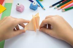 Les mains des enfants font le loup d'origami du papier de pêche Photos libres de droits