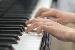 les mains des enfants jouent le piano La main de l'enfant sur des clés de piano image libre de droits
