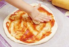 Les mains des enfants malaxent la pâte de pizza sur un tapis de silicone photographie stock libre de droits