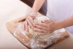 Les mains des enfants malaxent la pâte sur une planche à découper en bois Plan rapproché recette de la pâte, faisant cuire la tec photographie stock libre de droits