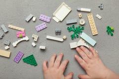 Les mains des enfants ont joué avec les briques en bois colorées images stock