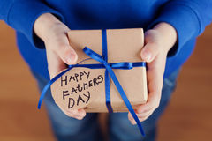 Les mains des enfants tenant un cadeau ou une boîte actuelle avec le papier d'emballage et l'étiquette attachée de ruban bleu le  Photographie stock