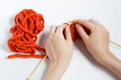 Les mains des femmes avec des aiguilles de tricotage Images stock