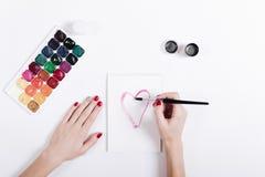 Les mains des femmes avec la manucure rouge ont peint le coeur d'aquarelle dans un aucun Photographie stock