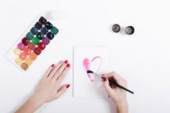 Les mains des femmes avec le vernis à ongles rouge ont peint le coeur d'aquarelle dans a Image libre de droits