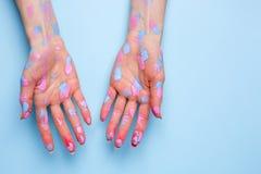 Les mains des femmes avec des traçages d'aquarelle sur le fond bleu photo stock