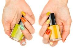 Les mains des femmes avec un vernis de clou coloré Images stock