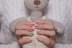Les mains des femmes avec une belle manucure de couleur et un jouet mou images libres de droits