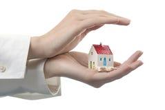 Les mains des femmes avec une maison Image stock
