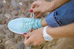Les mains des femmes avec une manucure rouge ont noué des dentelles sur la chaussure sportive Photographie stock