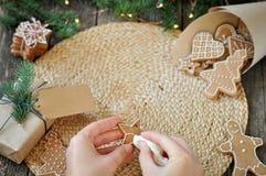 Les mains des femmes décorent les biscuits faits maison de pain d'épice de Noël avec du sucre se givrant sur un beau fond en bois photographie stock libre de droits